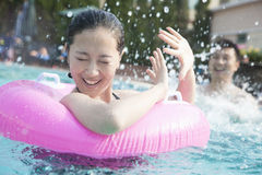 Young couple splashing and playing in the pool Royalty Free Stock Photo