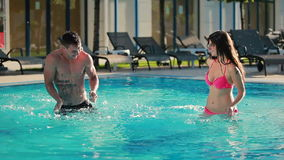 Young couple are splashing the water in the swimming pool stock footage