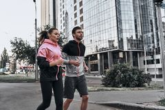 Morning jog. Young couple in sport clothing running through the city street together Stock Images