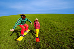 Young couple in sport wear snowboarding on the grass in the gree Royalty Free Stock Image
