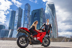 Young couple on a sports bike on the background of the city skyl Royalty Free Stock Image