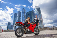 Young couple on a sports bike on the background of the city skyl Stock Photography