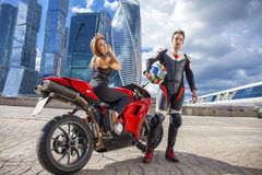 Young couple on a sports bike on the background of the city skyl Stock Photos