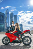 Young couple on a sports bike on the background of the city skyl Royalty Free Stock Photography