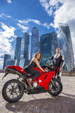 Young couple on a sports bike on the background of the city skyl Stock Image