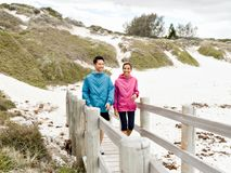 Young man and woman in sportswear walking at the beach Royalty Free Stock Photos