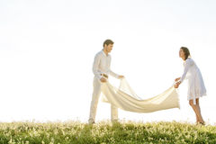 Young couple spreading picnic blanket on grass during sunny day Royalty Free Stock Image