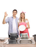 Young couple with stacks of clean plates making ok sign Royalty Free Stock Photos