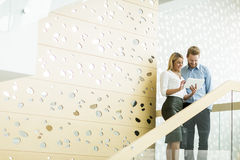 Young couple on stairs in office Royalty Free Stock Image