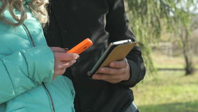 Young couple stand and hold the mobile phones stock footage
