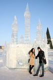 Young couple stand neat ice castle at winter day Royalty Free Stock Photography
