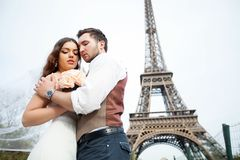A young couple standing against a background of the Eiffel Tower Royalty Free Stock Photo