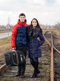Young couple standing arm in arm with luggage Stock Images