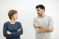 Young couple standing with arms crossed. Young couple standing with arms crossed and looking each other on white background stock photos