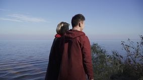 Young couple standing on the background of the water surface. Couple in love on a date outdoors. Relationship of a young stock video