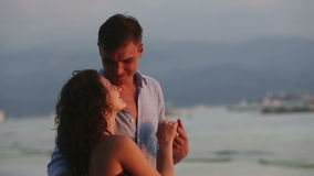 Young couple standing on beach and looking sunset. Young guy kisses the girl's hand, they stand on the beach near the sea, the sunset, the red light of the stock footage