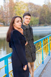 Young Couple Standing on Bridge in Park in Autumn Royalty Free Stock Photography