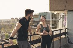 Couple relaxing after training. Young couple standing on a building rooftop terrace, relaxing after a hard workout stock photos