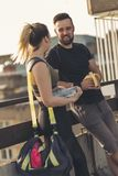 Couple relaxing after a workout. Young couple standing on a building rooftop terrace, relaxing and talking after a hard workout royalty free stock image