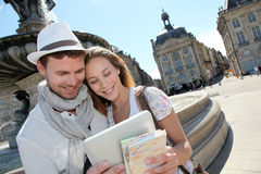 Young couple standing in city center looking at mep Royalty Free Stock Image