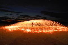 You got sparks?. Young couple standing close and spinning burning steel wool above their heads. Sparks flying around making visible its tracks. It is night time Royalty Free Stock Images