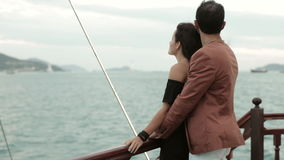 Young couple standing at deck of drifting vintage boat, talking and hugging stock video