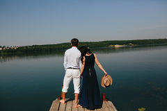 Young couple standing on a deck by the water. Looking into the distance Royalty Free Stock Photos