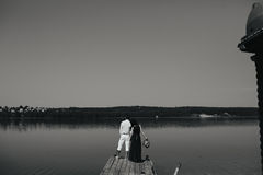 Young couple standing on a deck by the water. Looking into the distance Royalty Free Stock Image