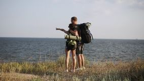 Young couple standing in embarrassing on the hill enjoying the view of sea. Backpack, hikers, travelers. Backside view stock video footage