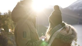 Young couple standing embrace kissing, looking landscape sunny winter day. Woman and man in warm clothes standing in