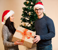 A young couple standing in front of the Christmas tree and givin Stock Photos