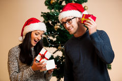A young couple standing in front of the Christmas tree and givin Stock Photo