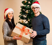 A young couple standing in front of the Christmas tree and givin Stock Images