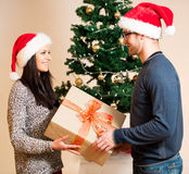 A young couple standing in front of the Christmas tree and givin Royalty Free Stock Images