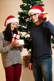 A young couple standing in front of the Christmas tree and givin Stock Photography
