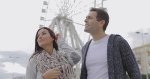 Young couple standing in front of a ferris wheel stock video