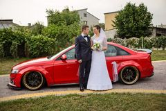 Young couple standing in front of a red car and looking at each other. The bride holding a bouquet of white flowers. They are going to a wedding ceremony Stock Images