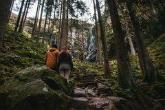 Young couple standing in front of a waterfall in the forest stock photography