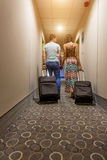 Young couple standing at hotel corridor upon arrival, looking for room, holding suitcases. Stock Photo