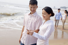 Young couple standing and looking at seashell on the beach, China Stock Images
