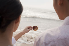 Young couple standing and looking at seashell on the beach, over the shoulder view Stock Images