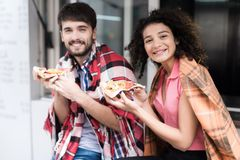 A young couple is standing by a mobile snack bar in the street. They ordered two pieces of tasty pizza and eat it Stock Images