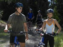 Young couple standing with mountain bikes. 2 young couple standing with mountain bikes royalty free stock photo