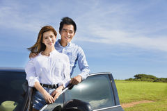 Young couple standing near the car and enjoy summer vacation Stock Images