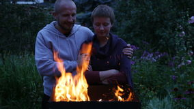 Young couple is standing near the fire stock video
