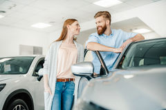 Young couple standing near new car and smiling each other stock image