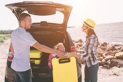 Young couple standing near the opened car boot with suitcases and bags. Dad, mom and daughter are traveling by the sea. Or the ocean or the river. Summer ride Stock Photo