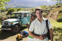 Young couple standing near parked jeep at start of camping holiday, woman embracing man, smiling, portrait Royalty Free Stock Photos