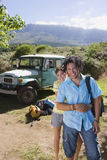Young couple standing near parked jeep at start of camping holiday, woman embracing man, smiling, portrait Royalty Free Stock Images