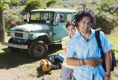 Young couple standing near parked jeep at start of camping holiday, woman embracing man, smiling, portrait Royalty Free Stock Photo
